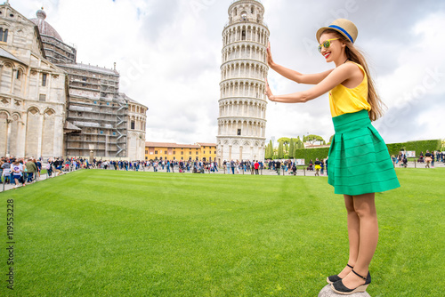 Fotografia, Obraz Young female traveler having fun in front of the famous leaning tower in Pisa old town in Italy