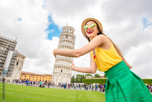 Obraz na plátne Young female traveler having fun in front of the famous leaning tower in Pisa old town in Italy