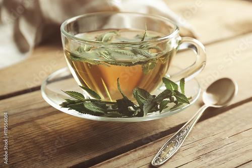 Fototapeta Cup of sage tea on wooden background obraz