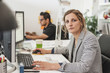 Portrait of female professional with colleague working in office