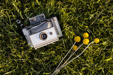 Overhead View Of Billy Buttons Daisies And Retro Styled Camera On Grass