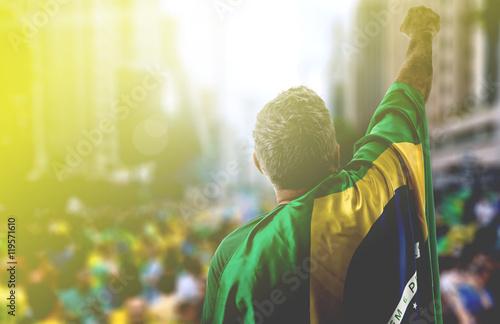 Fotografie, Obraz  Adult holding the flag of Brazil in Paulista Avenue