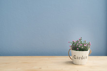 Wood Table With Pink Rose On Flower Pot And  Blue Cement Wall.