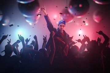 DJ or singer has hand up at disco party in club with crowd of people.
