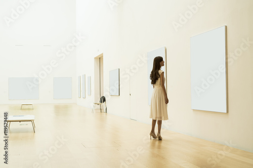 Fotografie, Obraz  Young woman is looking at the painting in the museum