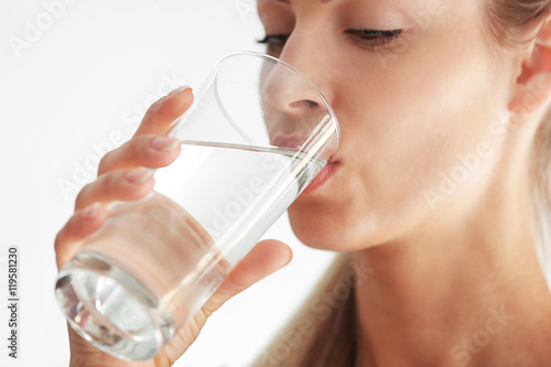 Beautiful girl drinking water on light background