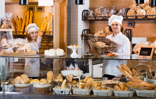 Foto op Plexiglas Bakkerij Portrait of cheerful positive smiling couple at bakery display