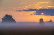 The foggy field on the background of sunset