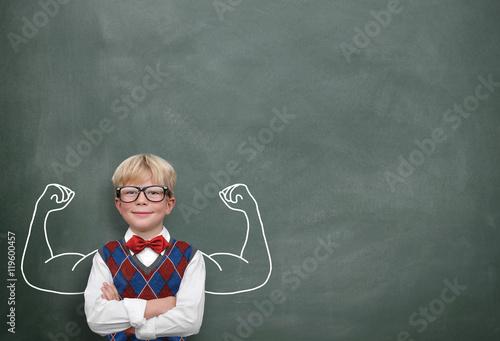 Fotografia  Kind mit Muskeln vor Tafel
