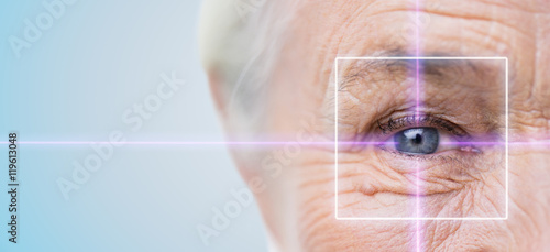 Fotografie, Obraz  close up of senior woman eye with laser light