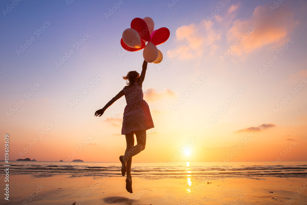 Fototapeta imagination, happy girl jumping with multicolored balloons at sunset on the beach, fly, follow your dream