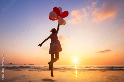 Fototapeta imagination, happy girl jumping with multicolored balloons at sunset on the beach, fly, follow your dream obraz