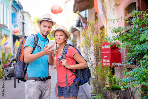 Travelers using smartphone. Young couple looking at phone traveling Asia.