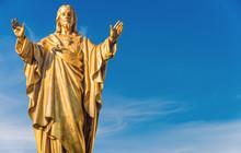 Old Jesus Christ Golden Statue Over Blue Sky
