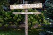 canvas print picture - Wooden wine tour sign with arrow with green shrubs on background