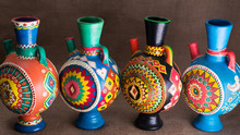 Four Decorated Colorful Handcrafted Pottery Jugs On Sackcloth Background