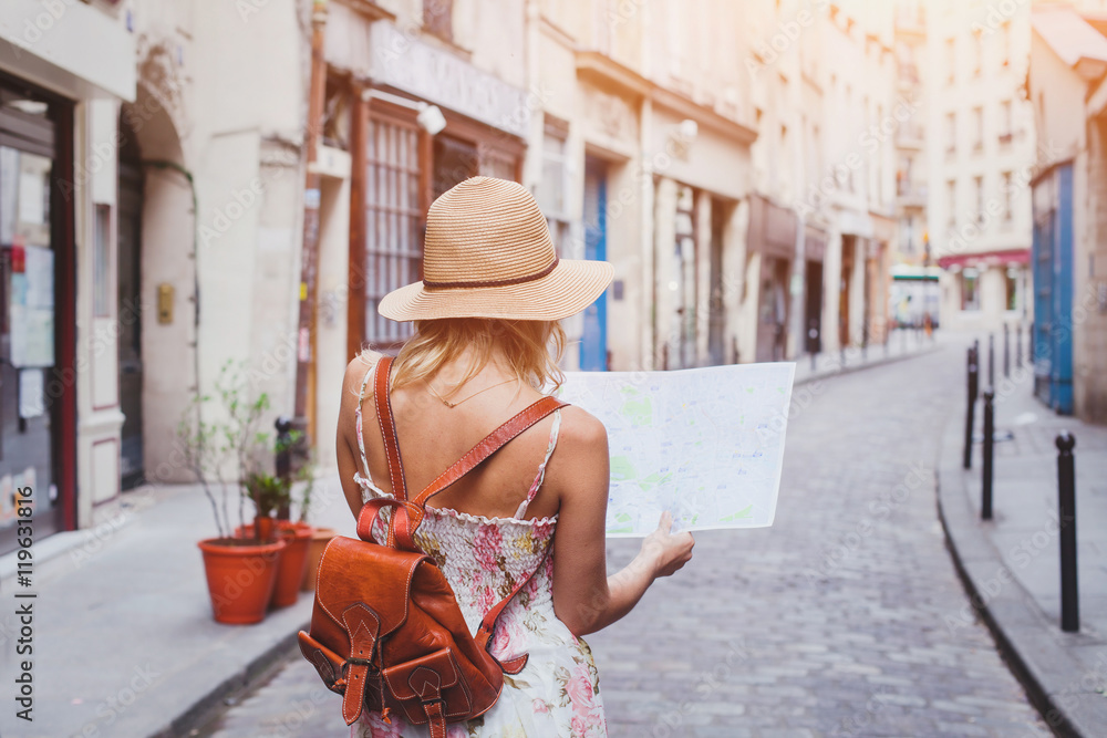 Fototapeta travel guide, tourism in Europe, woman tourist with map on the street