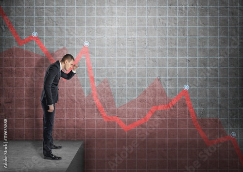 Fotografía  Businessman shading eyes with his hand looking at falling diagram