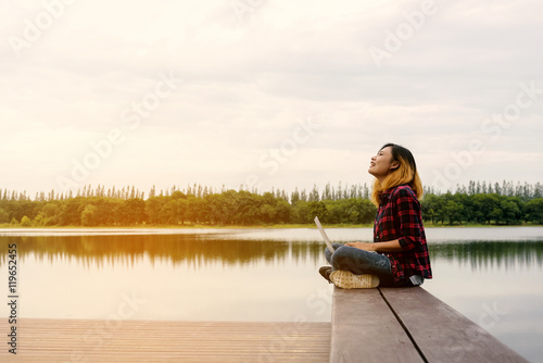 Photo  Mobile office - beautiful happy woman enjoying fresh air on wood