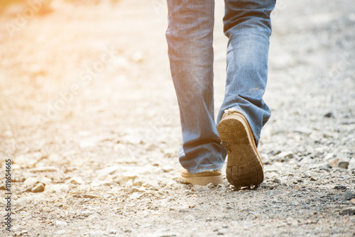 Foto  Lonely man wearing jeans and leather boots walking along the path strewn with rocks