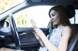 Young women are looking at the smartphone sitting in the driver's seat