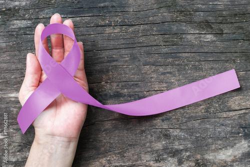 Lavender purple cancer (all kinds) awareness ribbon on human hand, aged wood bac Fototapet
