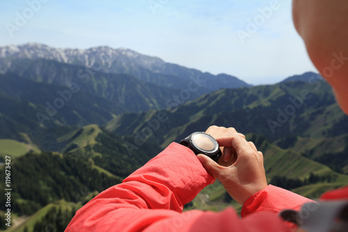 young woman hiker checking the altimeter on sports watch at mountain peak Canvas Print