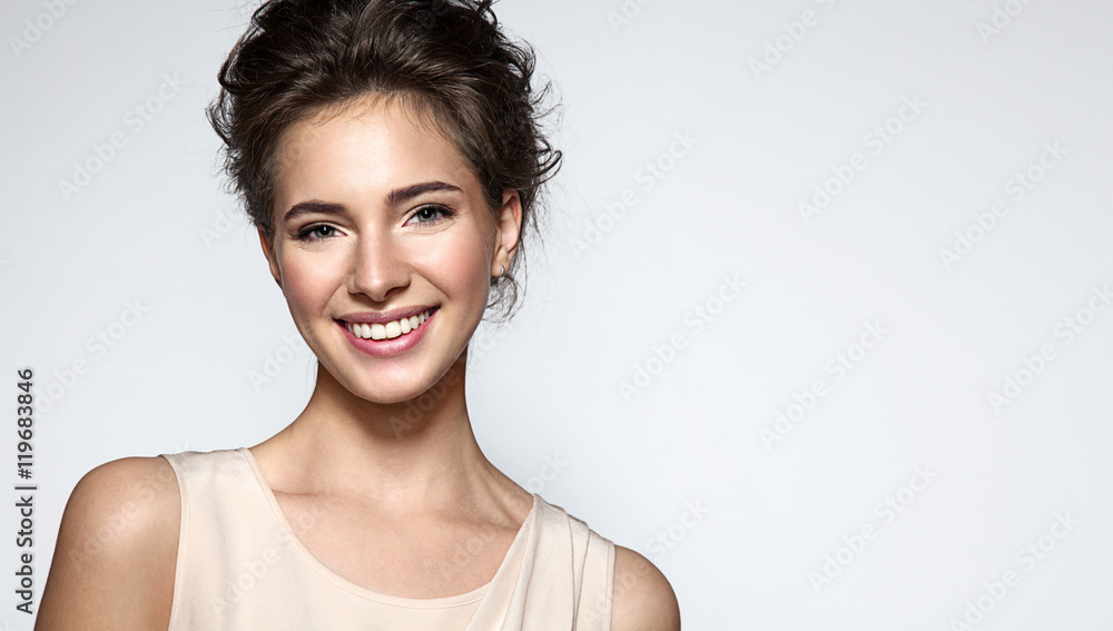 Fotografía Beautiful smiling woman with clean skin, natural make-up, and white teeth on gre
