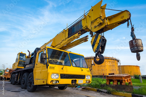 Fotografie, Obraz  Yellow mobile crane against fuel oil storage tank area in power