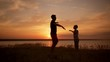 Silhouettes of dad and son playing, rejoicing in field at sunrise. Slow motion.