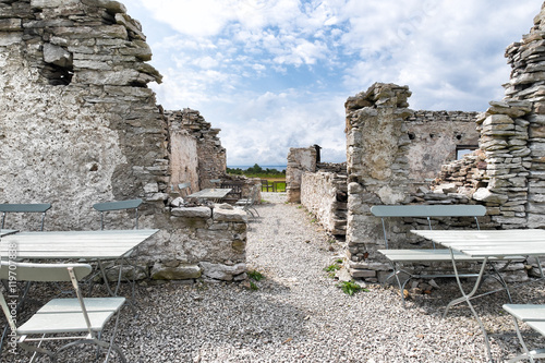 Photo  Cafe tables and chairs next to ancient ruins Sweden Gotland