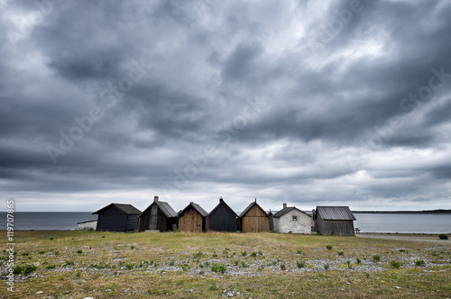 Fotografía  Row of old fishing shacks on the Baltic Sea under stormy sky