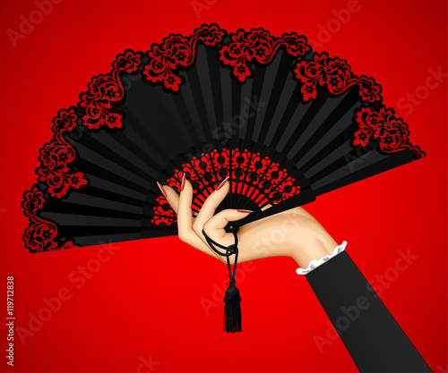 Photographie  Female hand with open black vintage fan isolated on red light