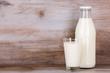 canvas print picture - Milch im Glas und in der Flasche auf Holz Stein Hintergrund.