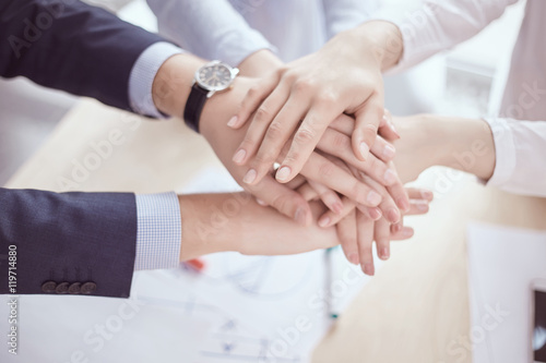 Fototapety, obrazy: team of businessmen and businesswomen with folded hands, a symbo