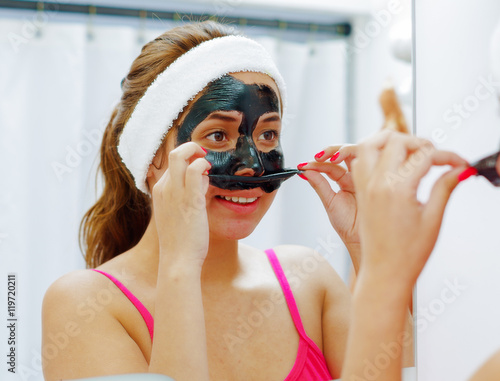 Poster Attraction parc Attractive young woman wearing pink top and white headband, removing black mask treatment from face using hands, looking in mirror smiling