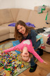 Mother and young daughter play in living room