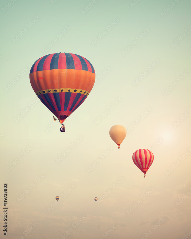 Vintage hot air balloon flying on sky with fog - retro filter effect style