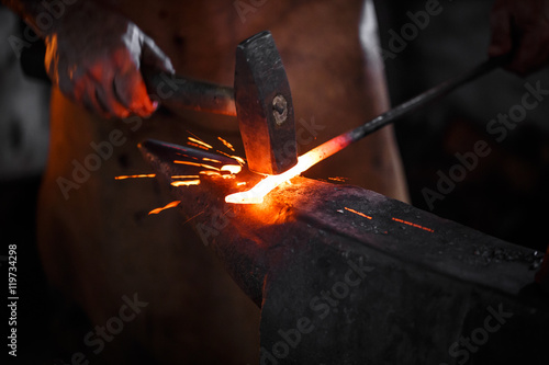 Photo Blacksmith manually forging the molten metal