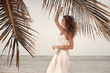 Beautiful woman in white dress on beach. Warm summer tones.
