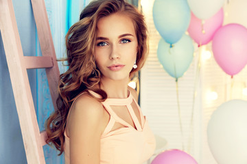 Naklejka fashion interior photo of beautiful young girl with dark curly hair and tender makeup, posing with colorful air balloons