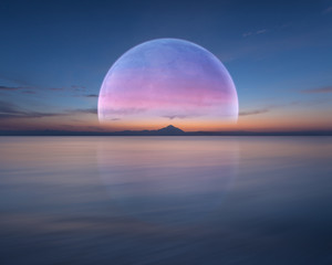 FototapetaPink planet like moon above the ocean and mountain
