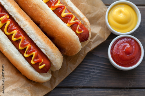 Fotografie, Tablou Barbecue Grilled Hot Dog with Yellow Mustard and ketchup on wooden table