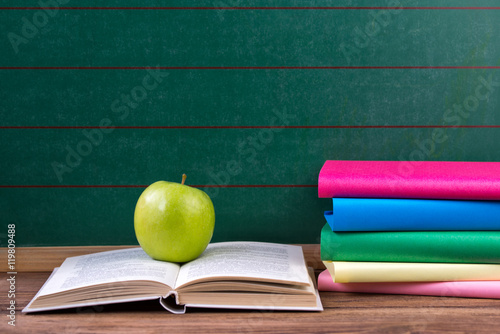 Apple And Colored Books On The Chalkboard Background