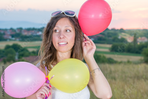Photo  Young woman holding balloons at sunset