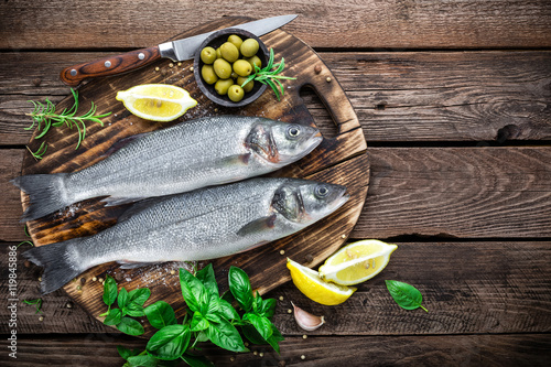 Tuinposter Vis raw seabass fish on wooden background top view