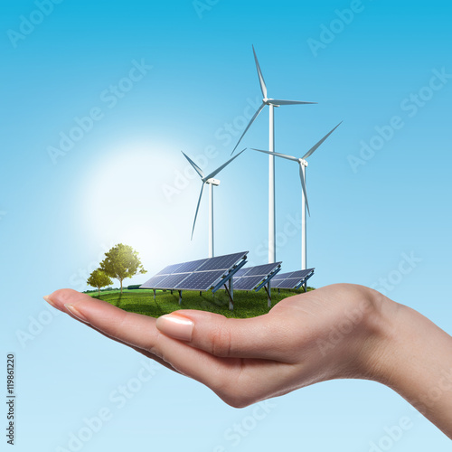 Fotografía  Wind turbines and solar panels in female hand