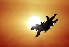Jet Fighter Flying Under Sunset