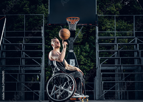Photo  Cripple basketball player in wheelchair plays basketball.