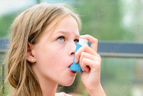 Girl uses an inhaler during an asthma attack Wallpaper Mural